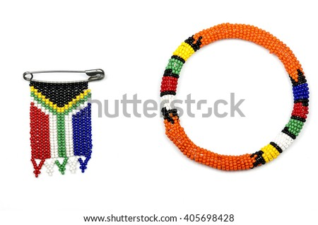 Colorful Zulu beads threaded into an armband and a south african flag on white
