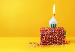 Colorfull birthday cake with red sprinkles and  one candle on a yellow background with copyspace. Festive background, birthday.