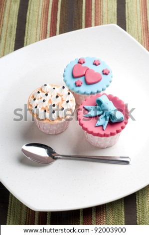 Colorfull cup cake on white plate isolate stripe background - stock photo