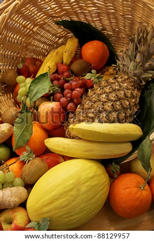 Colorfull fruit basket with oranges, bananas, grape, apples and kiwi