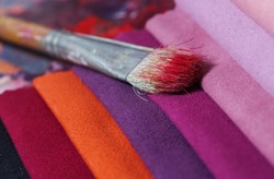 colorfull textile lies on a colorfull palette of the artist.Colored brushes and fabrics.