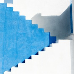 Colorfully painted staircase with contrast blues and whites. building shadows make this image an abstract background.