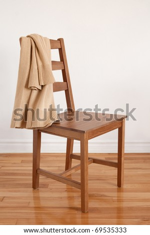 Colors of natural wood. Chair on wooden floor with clothing put over its back.