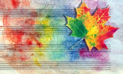 Colors of rainbow. Melody concept. Old music sheet in colorful watercolor paint and fallen maple leaf. Music concept. Abstract colorful watercolor background. Autumn melody