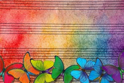 Colors of rainbow. Melody concept. Old music sheet in colorful watercolor paint and multicolored morpho butterflies. Music concept. Abstract colorful watercolor background.