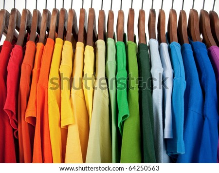 Colors of rainbow. Variety of casual clothes on wooden hangers, isolated on white.