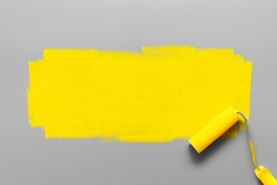 Colors of the year 2021 Ultimate Gray and Illuminating Yellow. Paint roller painting a yellow stripe on a gray background. Minimalistic composition with copy space