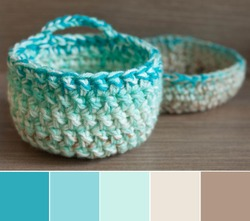 Colors of yarn basket bowls - green, turquoise, creamy beige and brown, shallow depth of focus. Color palette swatches, fresh trendy combination of colors for styling, pastel delicate ground nuances.