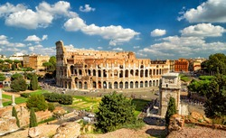 Colosseum (Coliseum) in Rome, Italy, Europe. It is main travel attraction of Rome. Panoramic scenic view of Rome with Colosseum in summer. Panorama of ancient Roman architecture in central Rome city.