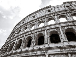Colosseum outside top arches part epic grayscale (black and white) view. Iconic ancient monumental 3-tiered Roman amphitheater, gladiatorial games arena in center of Rome, Italy