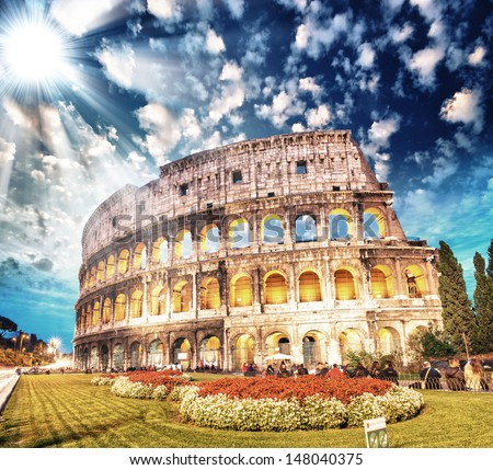 Colosseum - Rome. Sunset view with surrounding grass and park. - stock photo