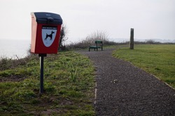 Colour image of a dog waste bin on a coastal path near to a park bench.