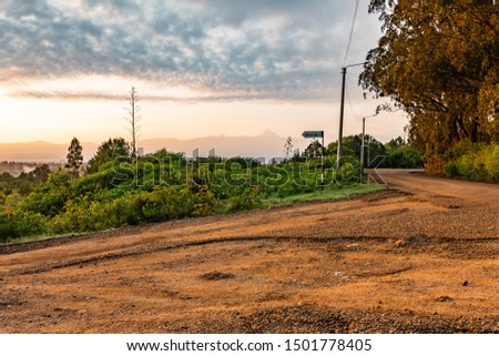 Colour landscape photograph of orange dusty road with the silhouette of Mount Kenya in background, taken in Kenya.