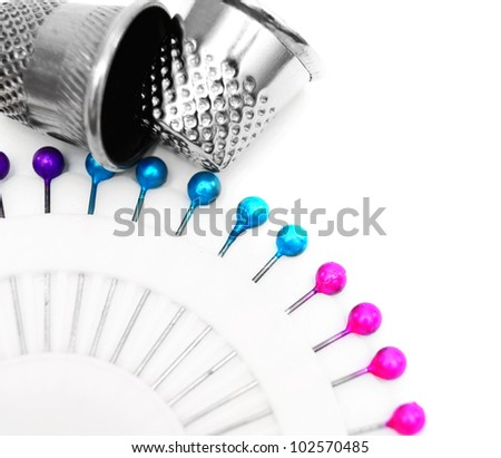 Colour needles and thimbles. On a white background.