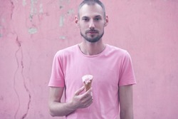 Colour obsession concept. Young handsome hipster guy with beard eating melting ice cream in waffle cone over pink background. Minimalistic style. Copy-space. Outdoor shot