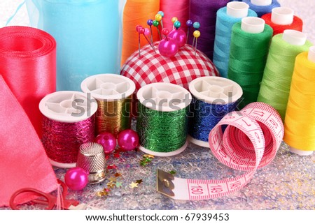 Coloured bobbins of threads, woolen balls and cushion for pins
