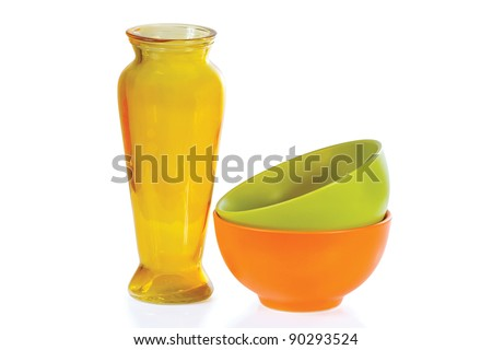 Coloured ceramic cups and vase on a white background