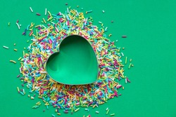 Coloured sprinkles with a heart-shaped cookie cutter on green paper background. Christmas love concept