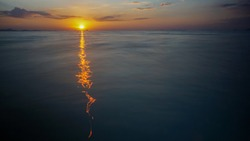 Colourful and beautiful sunset summer scenery over the open sea space with ocean waves breaking over the beach and sun rays reflecting over the water surface. Touristic tropical travel destinations.