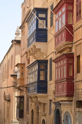Colourful balconies of ancient building in Valletta, Malta. This medieval city is built from the light sandy colour stones, and colourful balconies make it look vibrant and cozy.