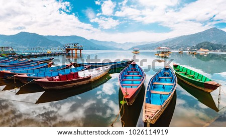 Colourful boats at shore of beautiful Phewa lake.  Pokhara, Nepal with Annapurna range in background. December 2017