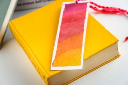 colourful bookmark on a closed yellow book. education. reading.
