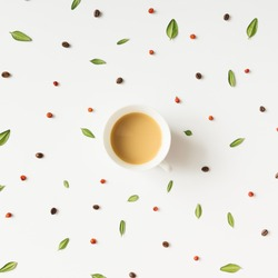 Colourful bright pattern made of  leaves, berries and coffee beans with coffee cup.