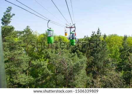 Colourful cabins on rope in the city park. Panorama of cablecars - electric cabin transport over the green trees in the park. #1506339809