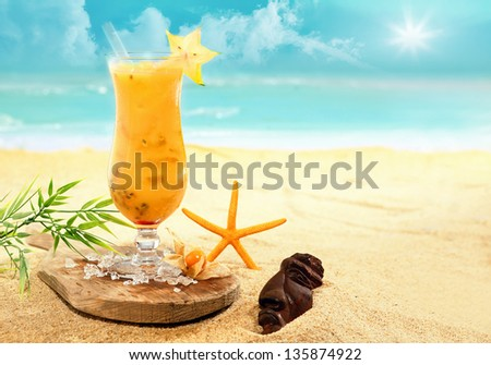 Colourful carambola and orange cocktail ina tall glass served on a wooden board on a golden beach at a tropical holiday resort during an enjoyable summer vacation