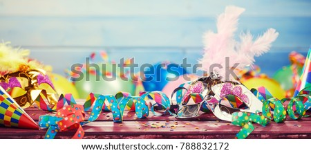 Colourful carnival panoramic banner with a jumble of party balloons, streamers, conical hats and confetti on a wooden table with copy space #788832172
