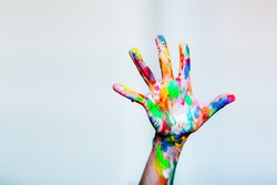 Colourful child's painted hand up on the white background