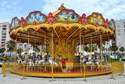 Colourful children's carousel with horses  in an amusement park. Empty old fashioned carrousel. Merry-go-round in Durres town, Albania