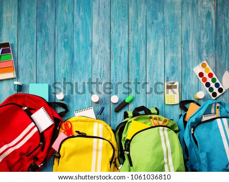 Colourful children schoolbags on wooden floor. Backpacks with school accessories