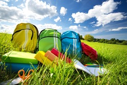 Colourful children schoolbags outdoors on the field. Backpacks with school accessories