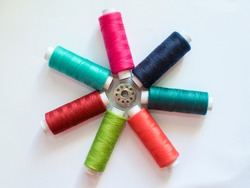 Colourful Cotton thread reels flat lay with circular arrangements with bobbin and white background.