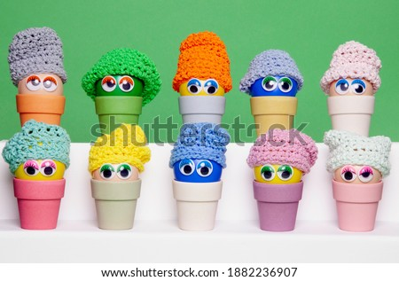 Photo of  Colourful Easter eggs, made of recycled plastic, with wobbly eyes and colourful knitted hats, aligned horizontally and sitting in  bamboo egg holders against an apple green background.