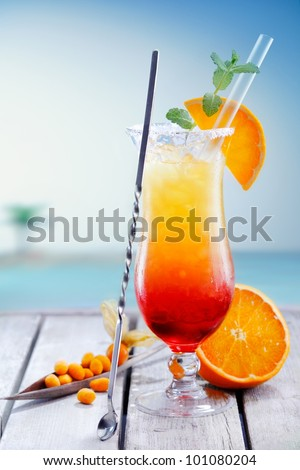 Colourful exotic Tequila Sunrise cocktail served on the rocks with crushed ice and a swizzle spoon