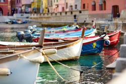 Colourful fishing boats in small marina of Vernazza, one of the five centuries-old villages of Cinque Terre, located on rugged northwest coast of Italian Riviera.