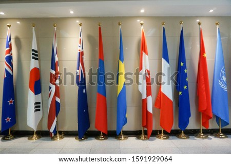 colourful flags of many nations (UK Korea, Australia China, UN, EU)