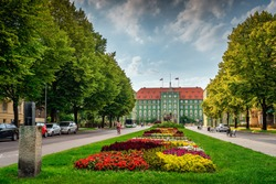 Colourful flowerbeds and tress on avenue of Pope John Paul II with green buildings of Szczecin City Council in the background