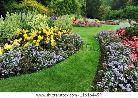 Colourful Flowerbeds and Winding Grass Pathway in an Attractive English Formal Garden #116164459