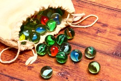 Colourful glass marbles and a cloth bag on a wooden background