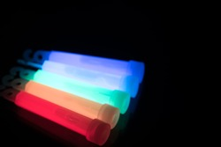Colourful glowsticks on a reflective surface