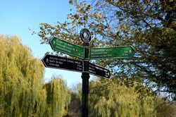 Colourful Grand Union Canal Walk and Capital Ring directions, Ballot Box Bridge, Perivale, England. On a sunny autumnal day with autumn/fall colours of trees in the background