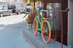 Colourful green and orange bicycle stands on the fence near entrance as a decoration. Decor. City. Style. Building. Outdoor. Urban. Shop. Cafe. Restaurant