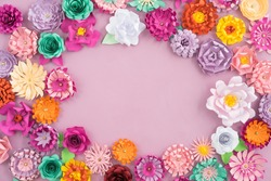 Colourful handmade paper flowers on pink background with copyspace in the middle