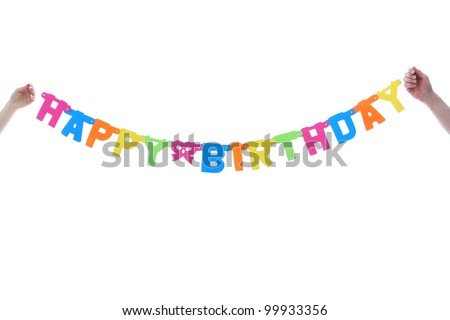 Colourful Happy Birthday banner being held midair by two hands in a celebration and party concept