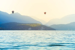 Colourful Hot air balloons flying over Annecy lake in the morning, France