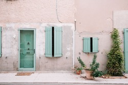 Colourful house wall facade, house with green door and shutters, Provence village, south France