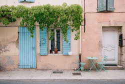 Colourful house wall facade, orange damages cracked walls, blue door and shutters, Provence village, south France